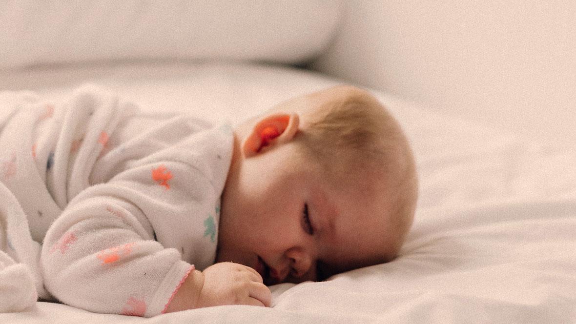 Baby liegt auf dem Bauch und schläft