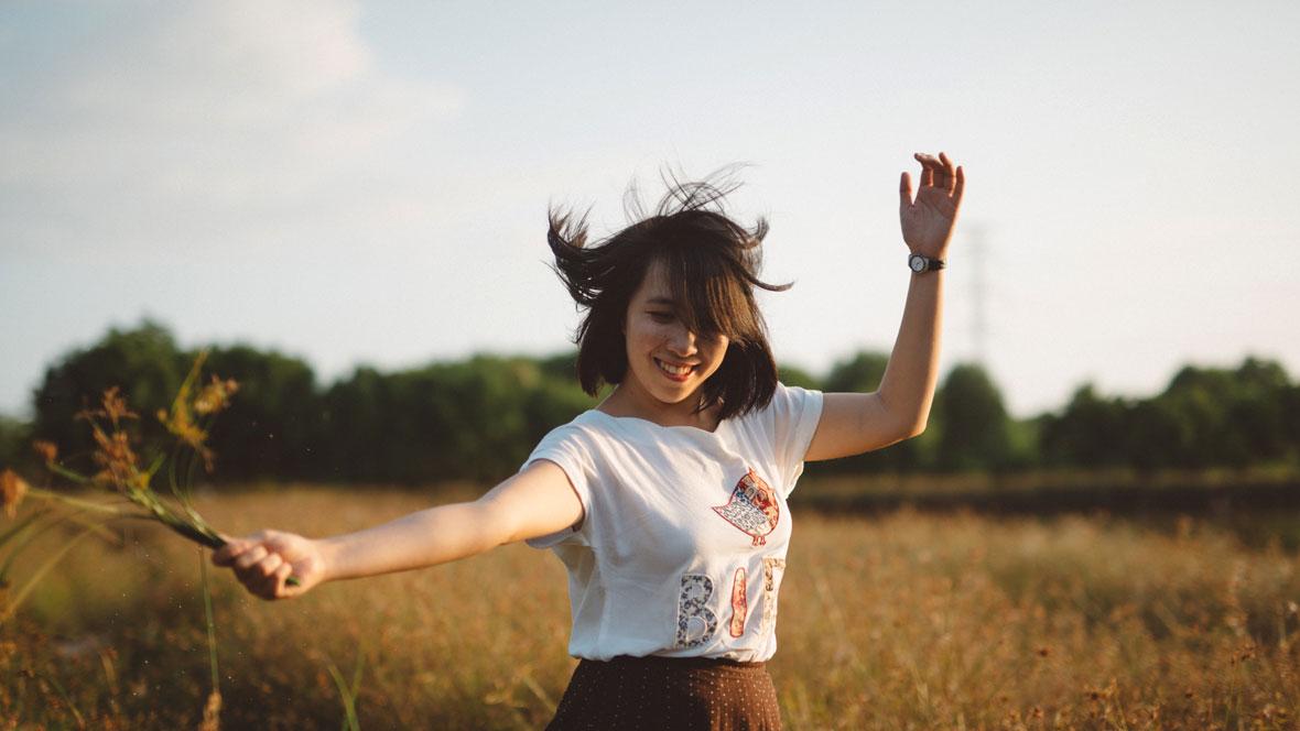 Frau läuft lachend über ein Feld