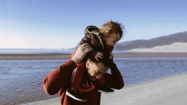 Ein vater trägt sein Kind auf den Schultern