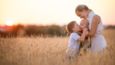 Mutter mit ihren zwei Kindern in einem Weizenfeld