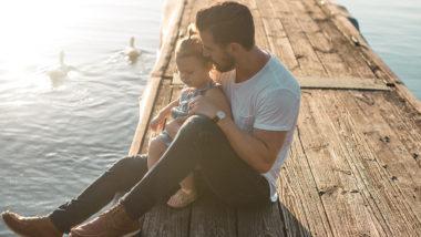 Vater und Tochter sind gemeinsam am See und sehen den Enten zu