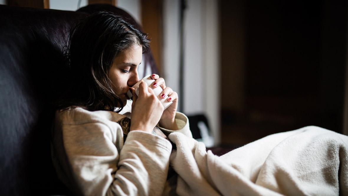Endometriose, Frau liegt mit Bauchschmerzen im Bett