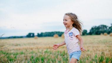 Kind rennt über Feld und Wiese
