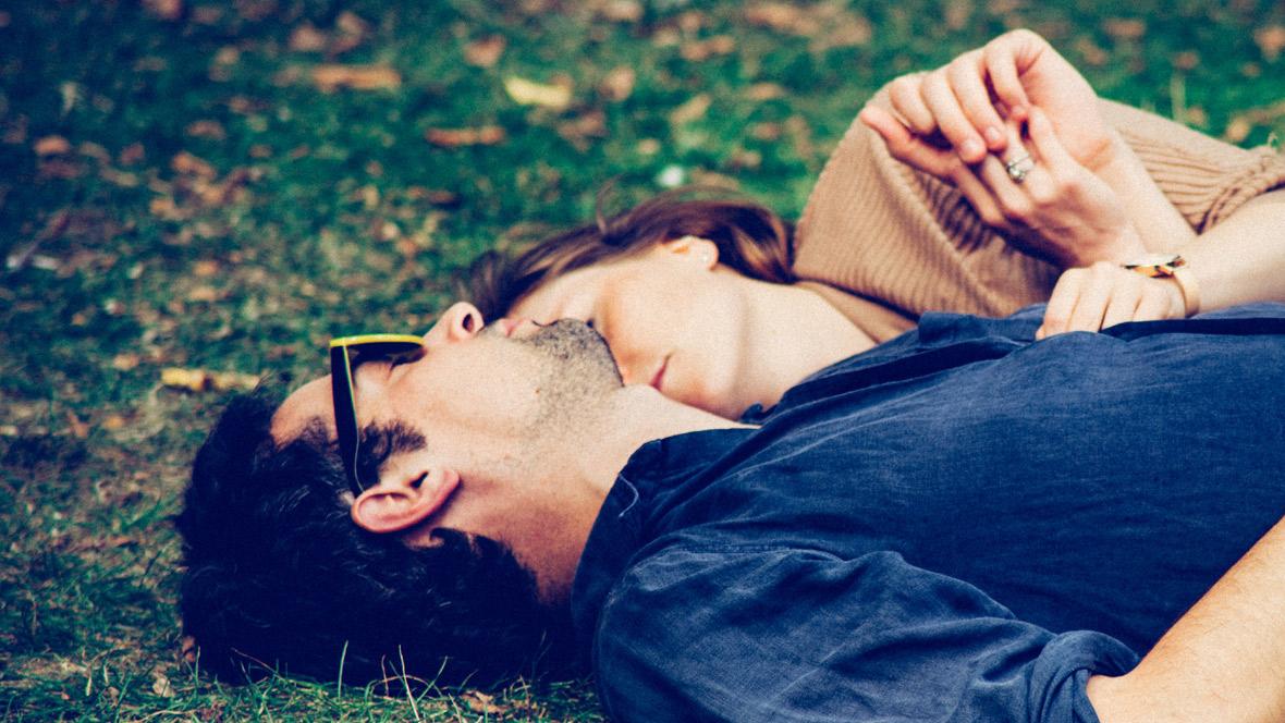 Frau und Mann liegen im Gras und schlafen