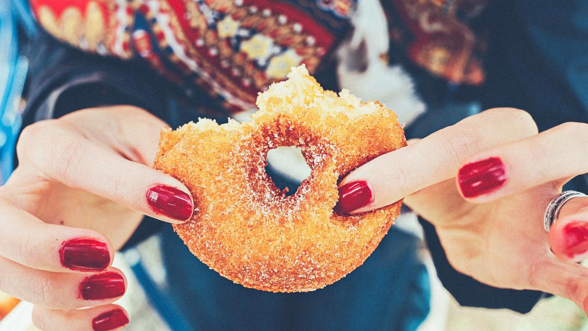 Zuckerkonsum, Frau hält Donut in der Hand