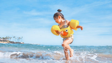Mädchen spielt mit Schwimmflügeln im Wasser