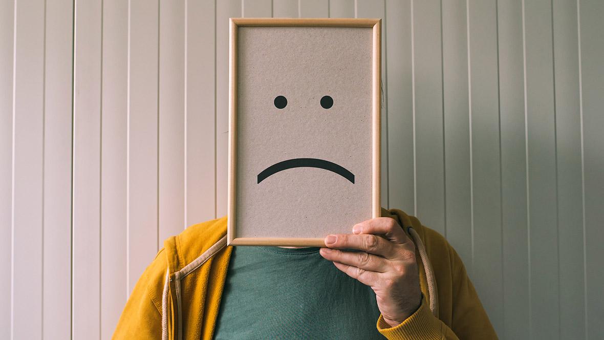 Mann hält sich traurigen Smiley vors Gesicht