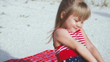 Kleines Mädchen sitzt am Strand