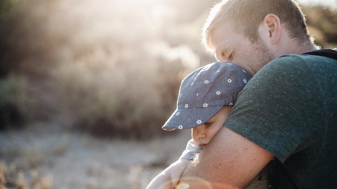 Vater trägt Baby vor der Brust
