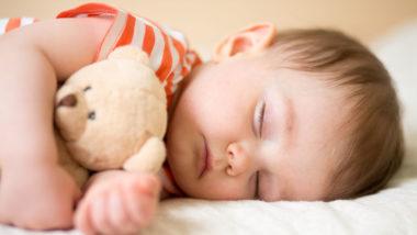 Baby schläft mit seinem Teddy im Arm