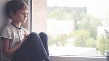 Kleiner Junge sitzt traurig auf der Fensterbank
