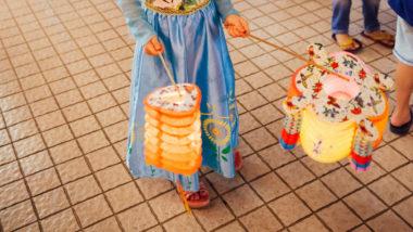 Laterne basteln: Ein Mädchen trägt zwei Laternen in den Händen